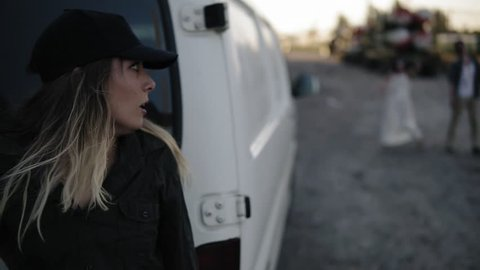 The scene of the scared girl runs away from the zombie, hiding behind the white van then run away. Two creepy zombies coming for her. Filming, halloween, horror concept