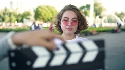 Attractive young actress with short wavy fair hair in white t shirt and pink sunglasses smiling to camera and touching her hair after clapperboard being used. Slider slow motion portrait shot