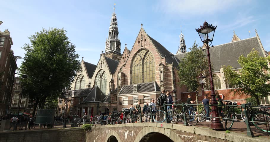 Amsterdam, Netherlands - September 2018: Peoples walking on the bridge in front of the Oude Kerk church