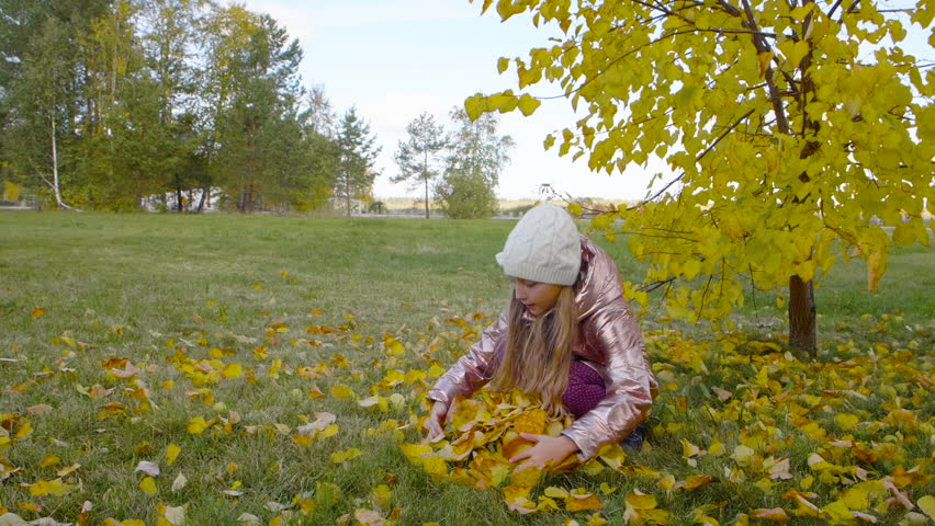 Happy cute girl grabbing yellow leaves in autumn park #1017013969