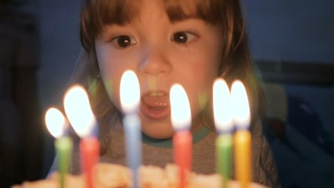 Little boy blows out candles on birthday cake at party. Closeup. Slow motion.