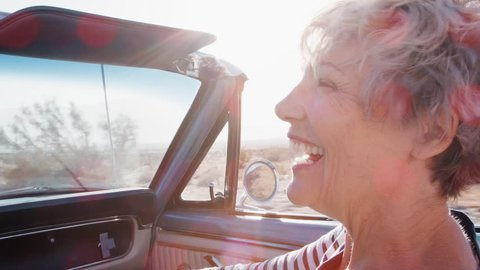 Happy senior female passenger in a convertible car, close up