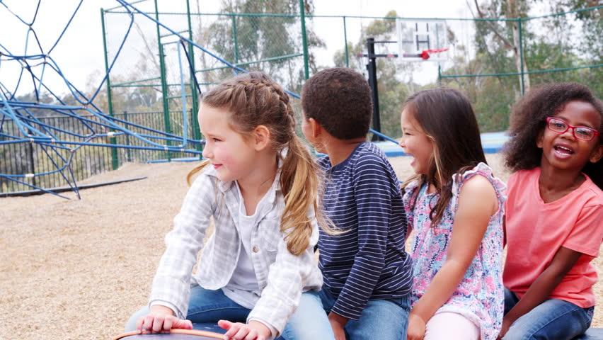 Elementary school kids spinning in a playground   Shutterstock HD Video #1017044569