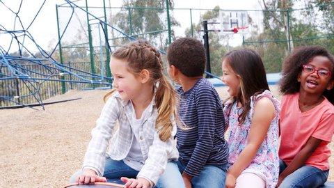 Elementary school kids spinning in a playground