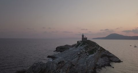 Aerial view at dawn of a lighthouse on the summit of a rocky islet without vegetation in front of Portoferraio, Elba island (Italy)