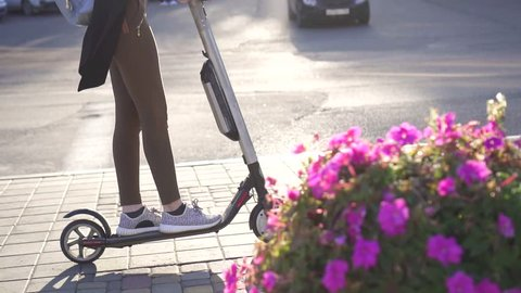 wooman rides an electric scooter on a Sunny city