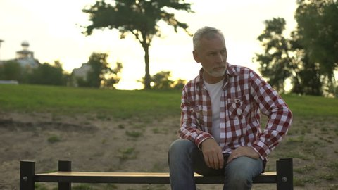Depressed old man sitting on bench, wife appearing beside, loss sorrow, memories