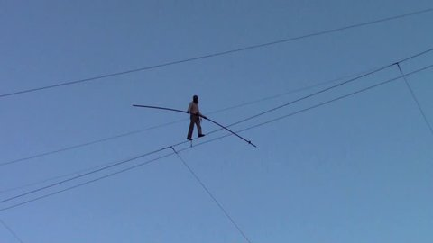 PERUGIA, UMBRIA, ITALY - DECEMBER 9, 2017: Funambulist Andrea Loreni crossing Piazza IV Novembre on a tightrope at a 40 metres heigth: In the middle of the sky