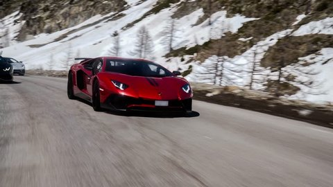 Eze, France- 04.17.2018: Rolling tracking shot driving Lamborghini Aventador Huracan mountain road in France chase speed snow