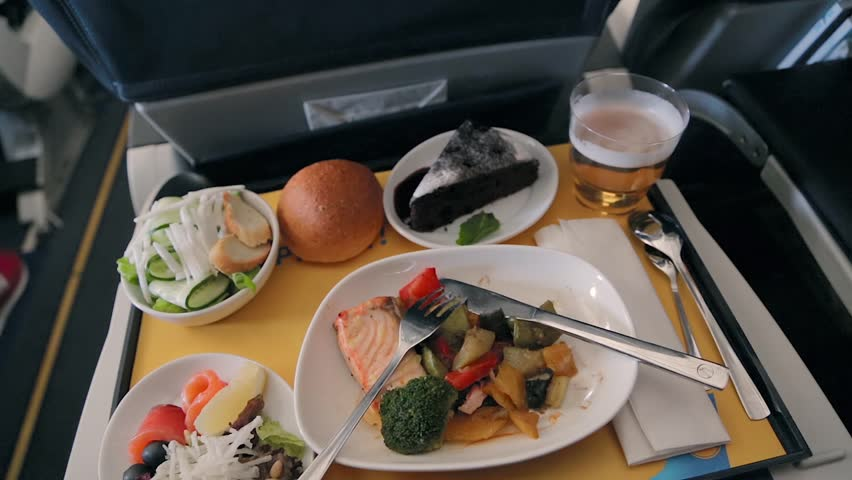 Food served on board of business class airplane on the table. Tray of food in the airplane. Tray of food on the plane, business class travel. Prepared food on the plane | Shutterstock HD Video #1017128959