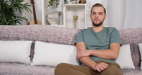 Upset Attractive Man Having a Hand Pain Suffer Alone While Sitting on Home Sofa