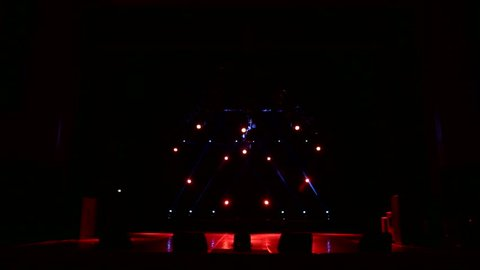 Red spotlights in the shape of a heart on an empty concert stage in the dark. Free stage with lights. Stage lights. Stage light and smoke.