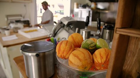 Close-up of a bowl of citrus fruit with a chef making pasta blurred out in the background.