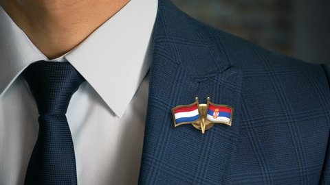 Businessman Walking Towards Camera With Friend Country Flags Pin Netherlands - Serbia