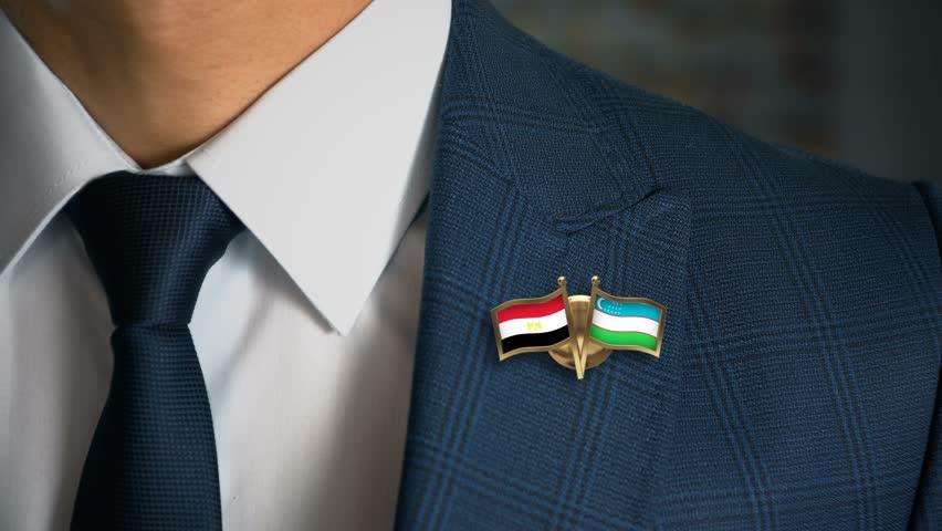 Businessman Walking Towards Camera With Friend Country Flags Pin Egypt - Uzbekistan