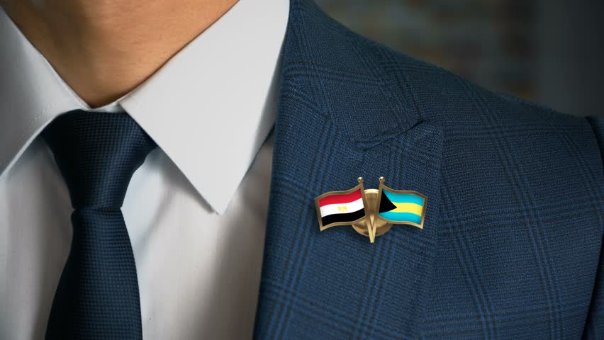 Businessman Walking Towards Camera With Friend Country Flags Pin Egypt - Bahamas