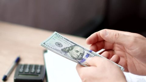 Male hands counting dollars banknotes above tax form.