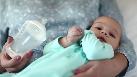 Three-month-old baby boy drank milk from a bottle, artificial feeding. Little baby boy on the hands of grandmother. Grandmother holds her grandson after feeding