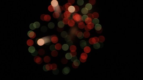 Beautiful bokeh of green, red and white fireworks balls at night sky holiday background Blurry firework sparkler