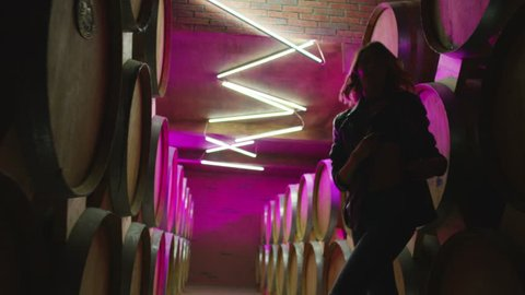 Hot girl dancing, walking . Dances with real strobe lights in colorful light winery with brandy , whiskey or wine barrels . Sexy body posing in wine house .  Clubbing scene in slow motion .