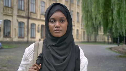 Young muslim african student in hijab holding backpack and smiling at camera, standing in park near university
