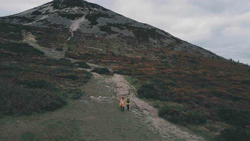 Epic aerial 4k shot of couple in yelow jackets hiking in mountains in dark cloudy weather. Ireland, Wicklow mountains.   Shutterstock HD Video #1017255769