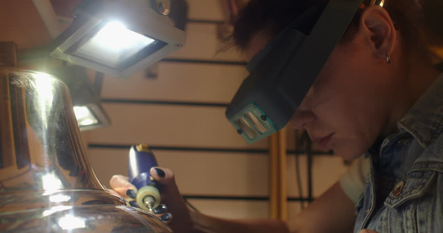 The engraver applies a texture to the inscription on the bell on the boarder. Woman engraver, engraving on the bell.