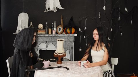 Horrifying woman in Death Ripper Halloween costume drinking tea with tender brunette at table in spooky decorated room