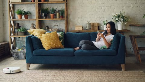 Attractive Asian girl is enjoying modern technology using smartphone and robotic vacuum cleaner sitting on sofa at home. Innovations and interiors concept.
