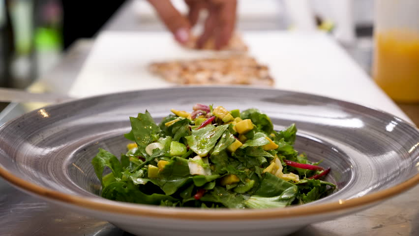 Cook hands placing fresh grilled meat on plate with avocado salad in restaurant kitchen