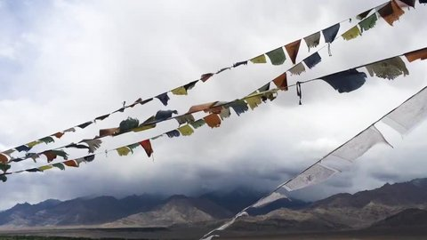 A real time shot of Tibetian prayer flags called Lung Ta waving in the cold wind with the mighty Himalayas in the background sorrounded by misty clouds, shot in Ladakh, India.