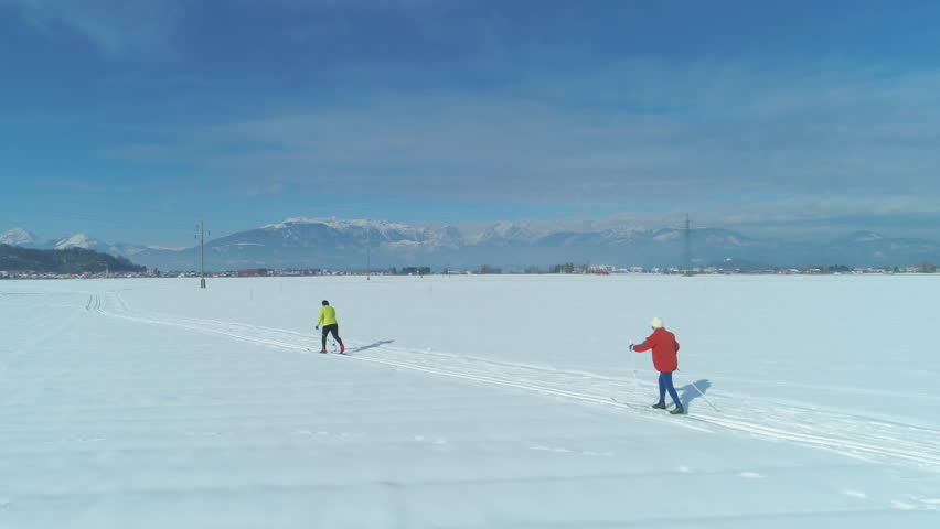 AERIAL: Two unrecognizable women skiing cross country in the idyllic sunny countryside on a perfect winter day. Picturesque mountains surround active female tourists skiing in spectacular Slovenia.