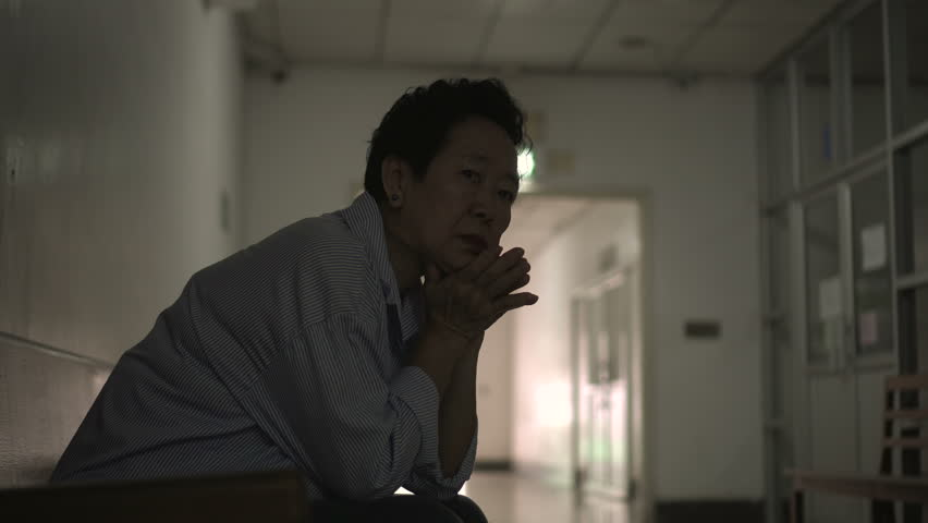 Asian senior woman waiting at hospital corridor worry and sad