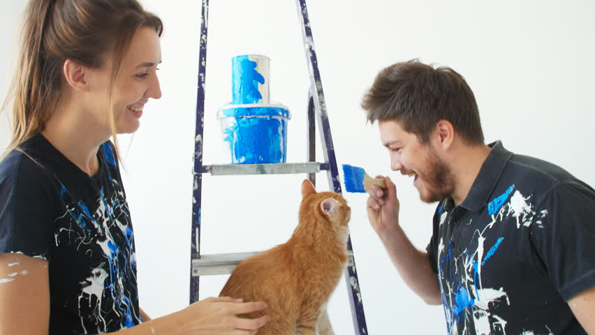 Repair, building and new home concept. Happy young couple with cat painting flat