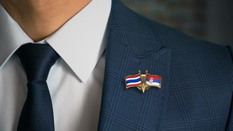 Businessman Walking Towards Camera With Friend Country Flags Pin Thailand - Serbia