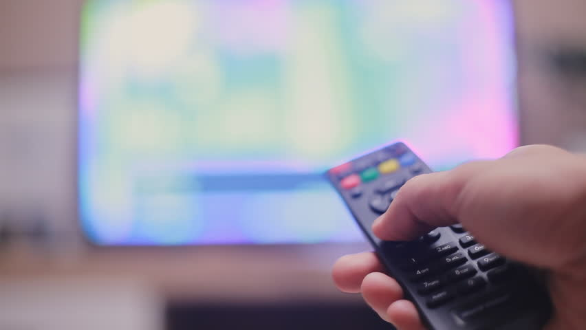 Male hand holding the TV remote control and changing television channels. Close-up and blurred background | Shutterstock HD Video #1017442219