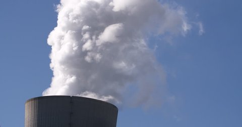 RWE power plant cooling tower working on lignite producing huge cloud of steam in Neurath, Germany, tilting shot, 4K