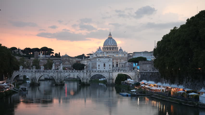 ROME, ITALY - AUGUST 14, 2018: Time lapse of traffic on St. Angelo bridge against St. Peter's Basilica in evening. The historical center of Rome is listed as UNESCO World Heritage since 1980 | Shutterstock HD Video #1017488809