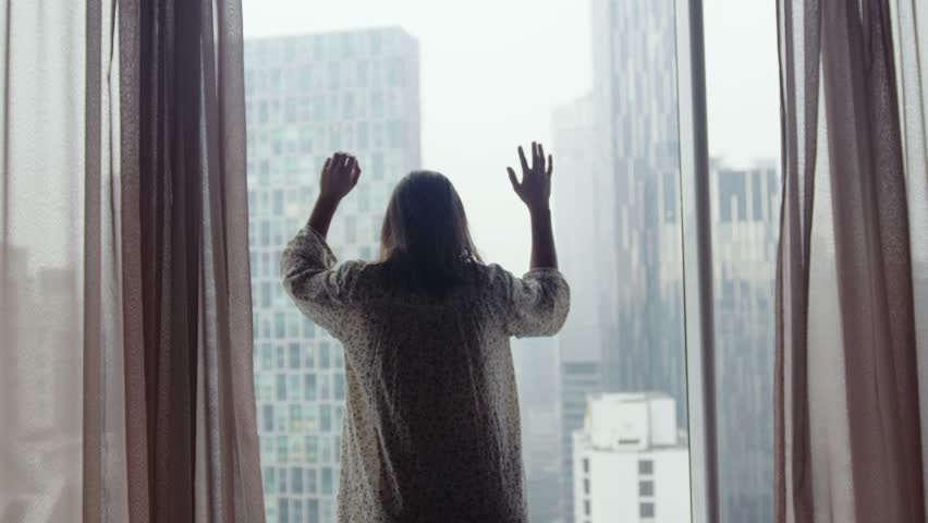 Sad neglected girl with dirty hair opens curtains looks in window on the curban architecture during rain. 3840x2160 | Shutterstock HD Video #1017501739