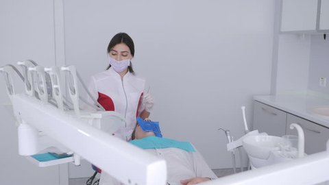 Dentist is treating patient in modern dental office. The operation is carried out using cofferdam.