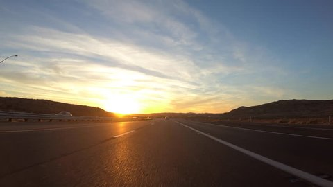 Driving into the sunset on Interstate 15 in the Mojave desert near Barstow, California.