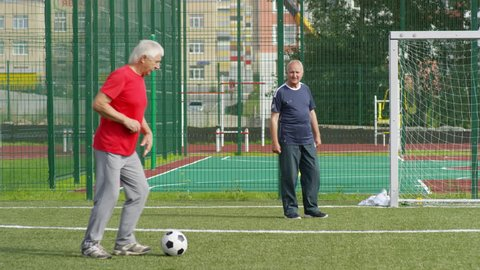 Group of retired men playing football outdoors and passing ball to each other while their friend standing at goal net and catching it