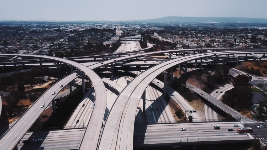 Drone flying around Judge Pregerson highway junction in Los Angeles, cars going over complex flyovers and intersections. | Shutterstock HD Video #1017541159
