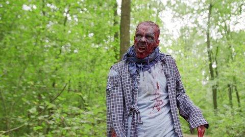 Zombies male are walking through the woods.