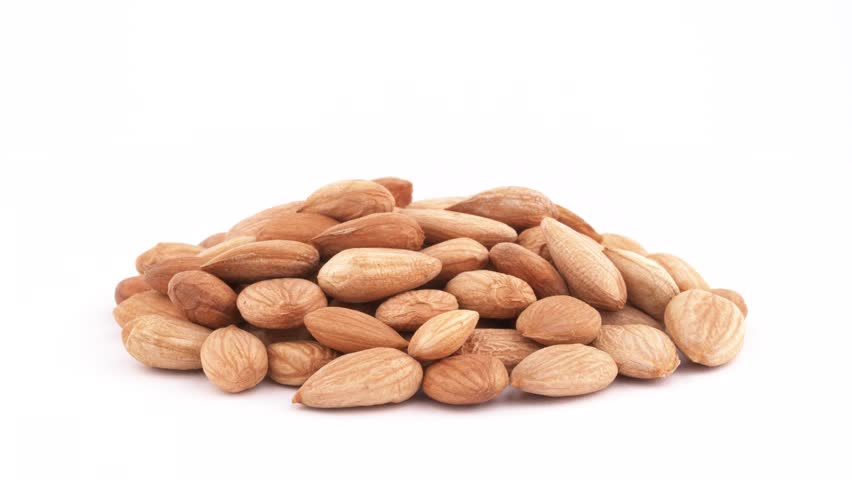 A pile of apricot kernels heap. Smoothly rotating on the turntable, isolated on the white background. Close-up. Macro.   Shutterstock HD Video #1017561349