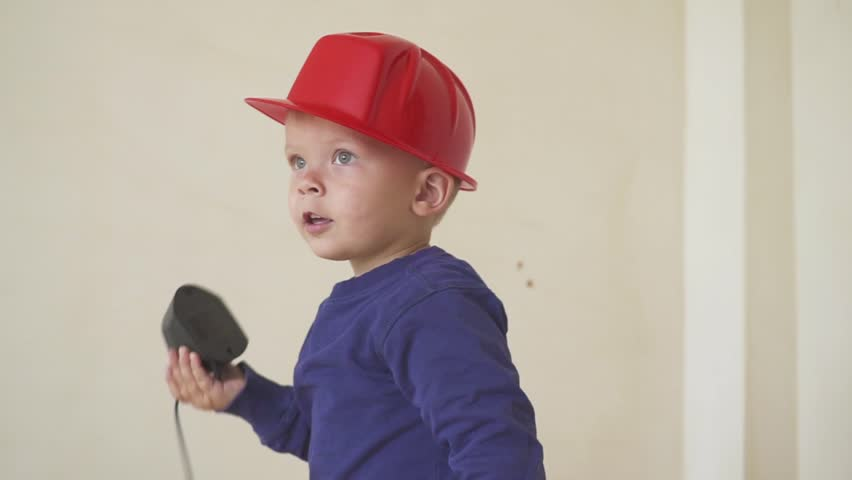 young cute builder boy in uniform and hard hat or helmet with electric  screwdriver against the background of construction and repair. 360b7af30f91