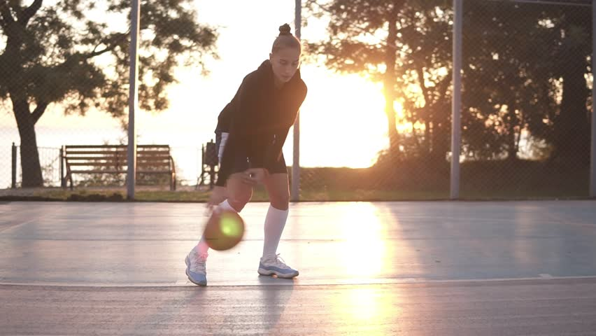 Close up footage of a young girl basketball player training and exercising outdoors on the local court. Young woman in white golf socks training cross bouncing with basketball ball