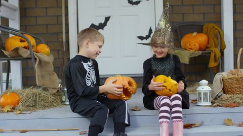 Happy little brother and sister dressed like witch and skeleton sitting on porch decorated for Halloween, playing with jack-o-lanterns and laughing