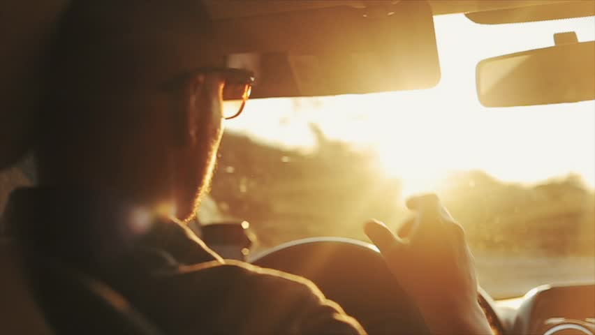 A close back view of a grown-up man in sunglasses driving a car during daytime. Bright sun shines in his eyes