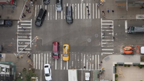 A top down bird's eye view of a typical Manhattan intersection as traffic and pedestrians travel on the streets below.
